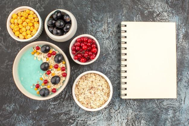 Caderno branco de frutas, tigelas de groselha, uvas, aveia, doces, doces, branco