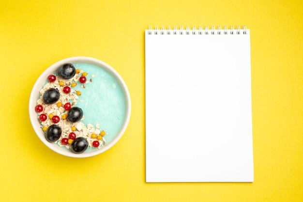 Caderno branco de uvas de groselha e uvas de groselha de cima em close-up