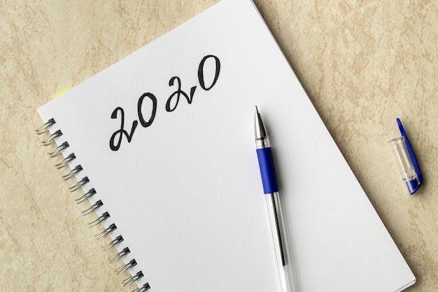 Caderno branco e a inscrição preta 2020. caneta azul em papel e boné em uma tabela