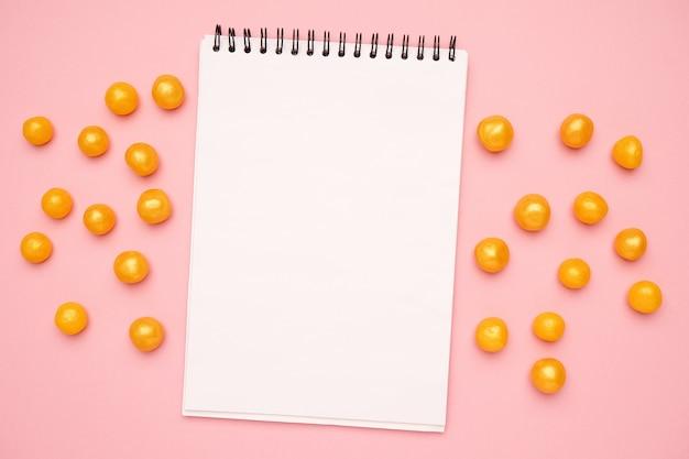 Caderno branco e doces amarelos doces em um rosa