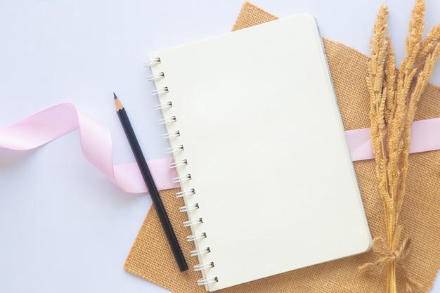 Caderno branco em branco com linha ou bloco de notas e lápis ou caneta preta perto de uma flor seca no fundo branco da mesa