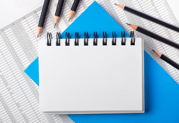 Caderno branco em branco com lugar para inserir texto na mesa ao lado de lápis pretos em uma superfície azul e relatórios
