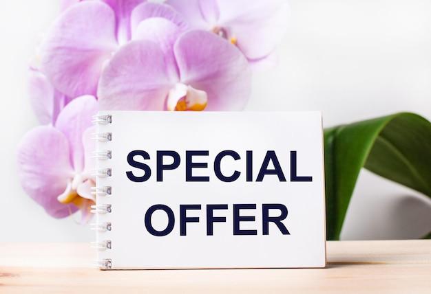 Caderno branco em branco com o texto oferta especial na mesa no contexto de uma orquídea rosa claro.