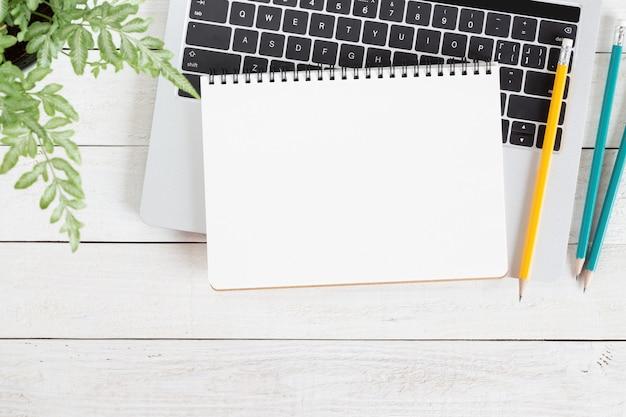 Caderno branco em branco no computador portátil na mesa de madeira