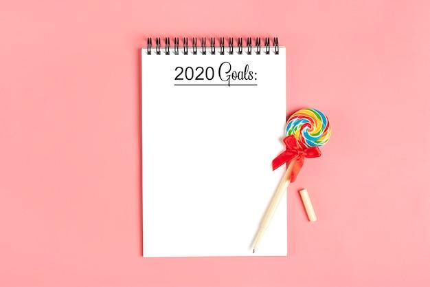 Caderno branco para notas, caneta - pirulito em fundo rosa plana leigos
