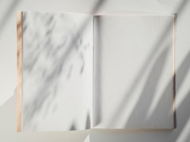 Caderno branco sobre um fundo branco com sombras de folhas