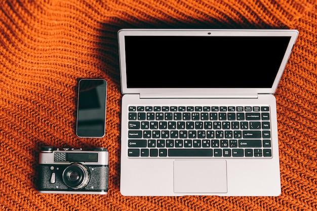 Caderno, câmera e telefone em fundo laranja. ambiente de trabalho