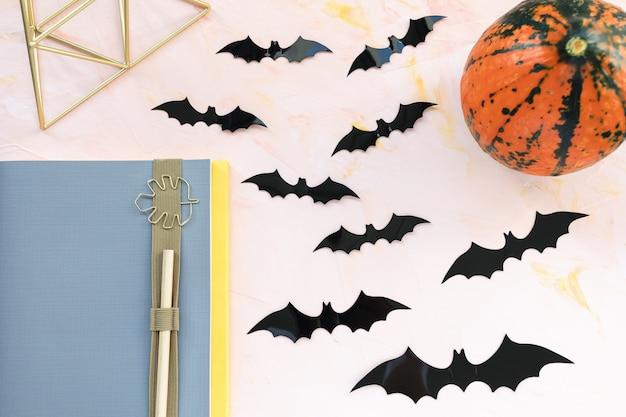 Caderno, caneta, abóbora e morcegos em rosa plano