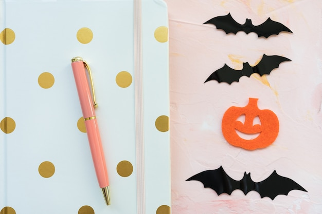 Caderno, caneta, abóboras e morcegos em rosa plano
