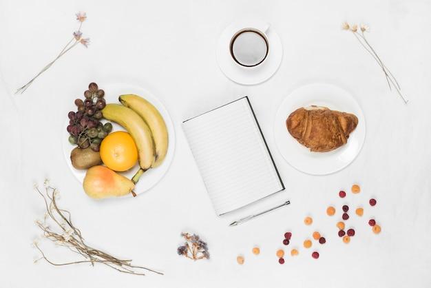 Caderno; caneta; croissant; frutas; café e flores secas em pano de fundo branco