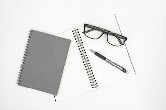 Caderno, caneta e óculos isolados no fundo branco.
