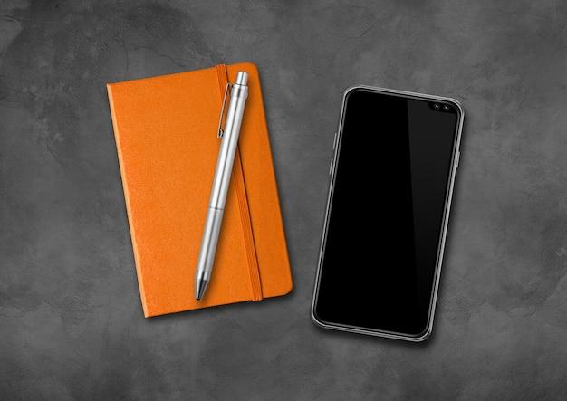 Caderno, caneta e smartphone em uma mesa de concreto