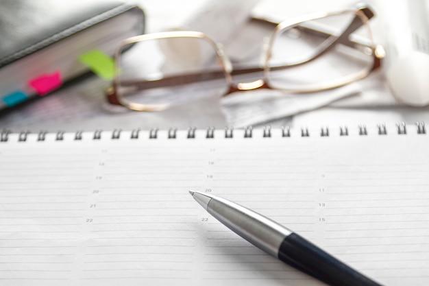 Caderno, caneta, óculos, documentos financeiros na área de trabalho.