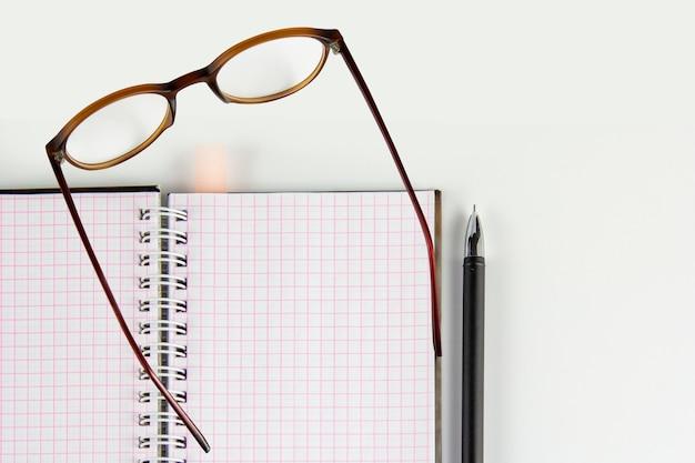 Caderno, caneta, óculos na mesa branca