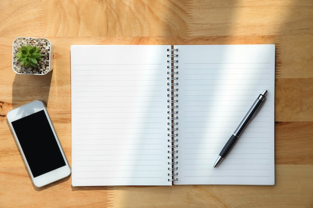 Caderno, caneta, planta verde e smartphone em fundo de madeira