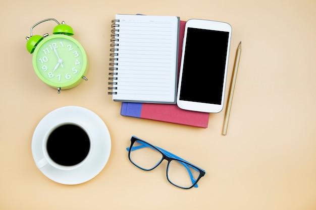 Caderno capa vermelha celular calculadora preto café copo branco óculos azuis