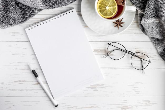 Caderno, chá, caneta, óculos em uma mesa de madeira branca