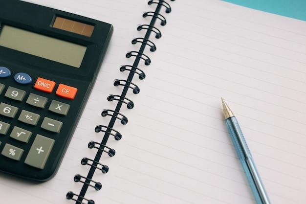Caderno claro, caneta e uma calculadora em um fundo azul