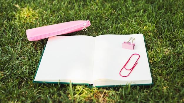 Caderno com artigos de papelaria rosa na grama