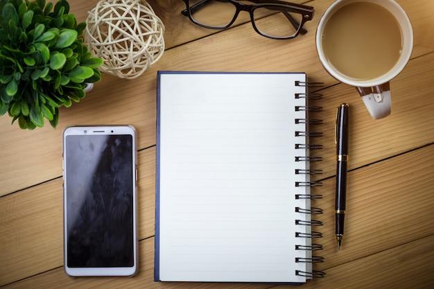 Caderno com as páginas em branco na tabela de madeira.