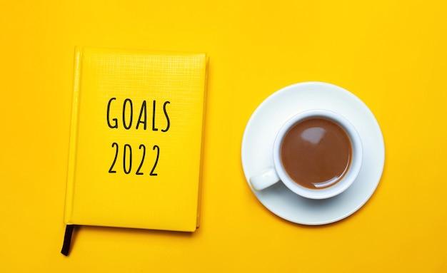 Caderno com as palavras metas 2022 e uma xícara de café