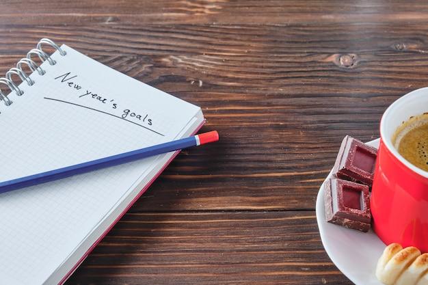 Caderno com as palavras metas de ano novo escritas com um lápis azul e vermelho em cima de placas de madeira rústicas marrons com uma xícara de café ao lado