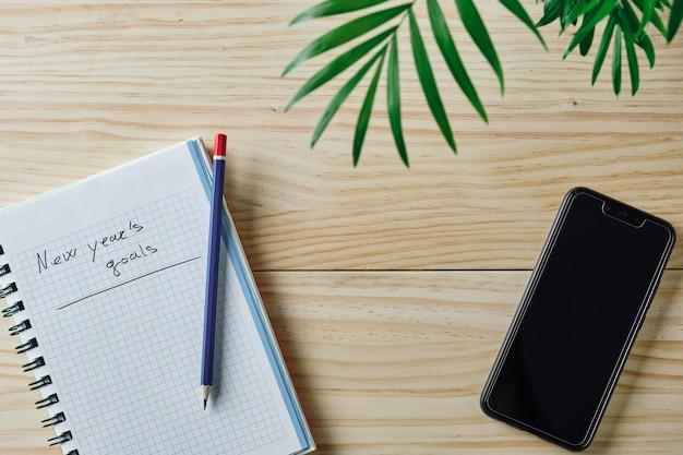 Caderno com as palavras metas de ano novo escritas em um fundo de madeira natural com um lápis azul e vermelho na parte superior, algumas folhas verdes na parte superior e um smartphone ao lado