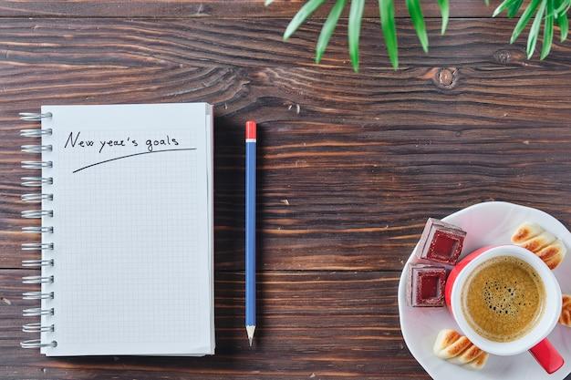 Caderno com as palavras metas de ano novo escritas em um fundo rústico de madeira marrom com um lápis azul e vermelho ao lado, algumas folhas verdes em cima e uma xícara de café no canto