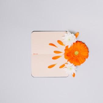 Caderno com botões de flores brilhantes na mesa