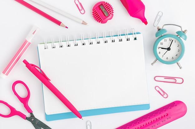 Caderno com branco em branco, artigos de papelaria coloridos e relógio no fundo branco. conceito de educação. maquete, configuração plana