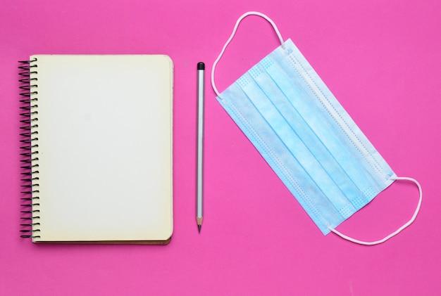 Caderno com caneta, atadura de gaze em fundo rosa, vista superior