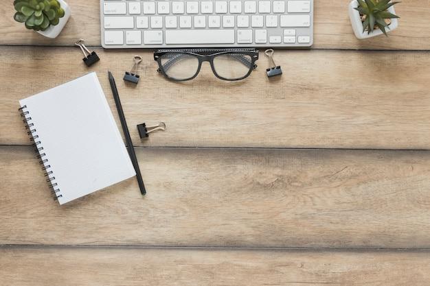 Caderno com caneta colocada perto de teclado e óculos na mesa de madeira