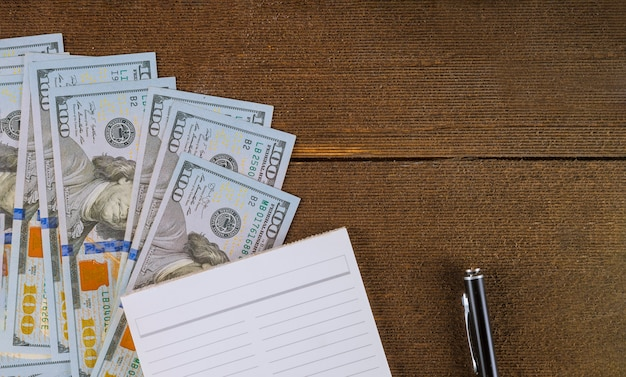 Caderno com caneta e dólares.