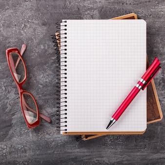 Caderno com caneta e óculos
