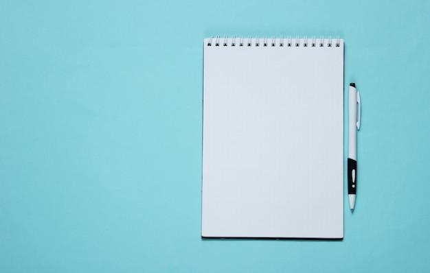 Caderno com caneta em papel azul