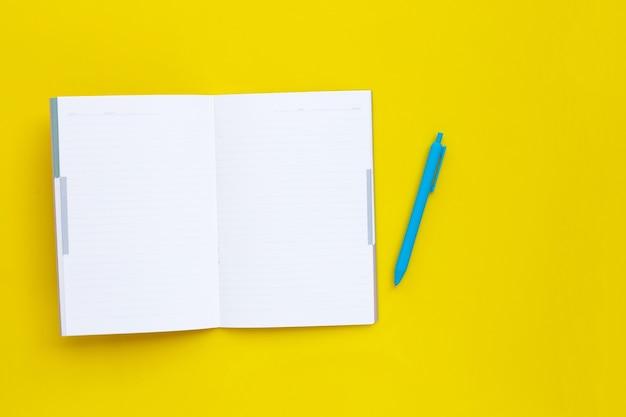 Caderno com caneta na superfície amarela