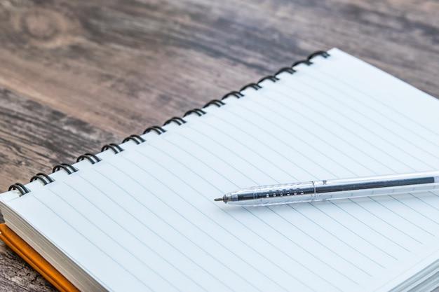 Caderno com caneta no fundo escuro de madeira