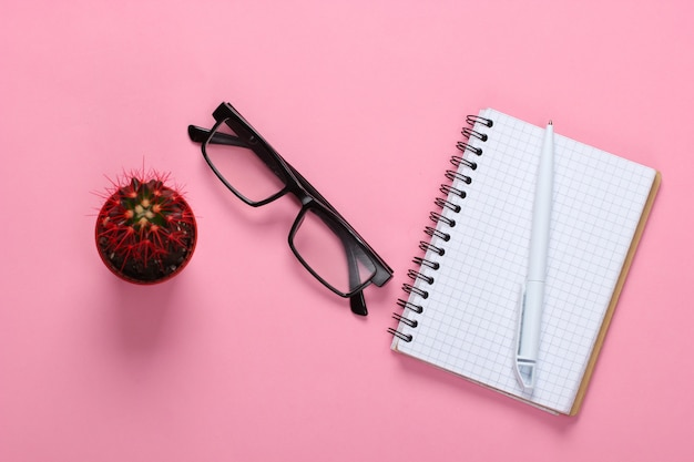 Caderno com caneta, óculos, cacto em rosa pastel. espaço de trabalho