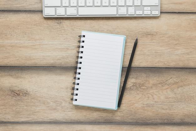 Caderno com caneta perto de teclado na mesa de madeira