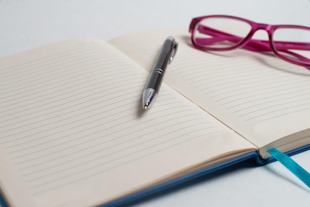 Caderno com caneta preta e óculos violetas na mesa
