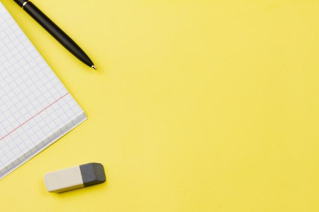 Caderno com caneta sobre fundo amarelo.