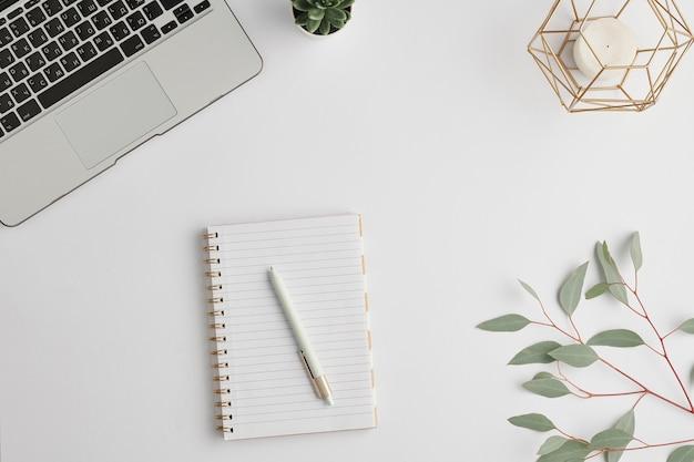 Caderno com caneta, vela, pequena planta doméstica, ramo com folhas verdes e teclado de laptop na mesa branca
