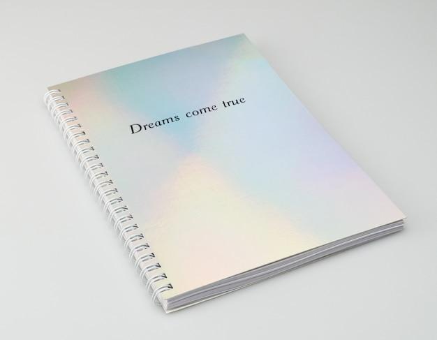 Caderno com capa iridiscente e texto motivacional, fundo branco