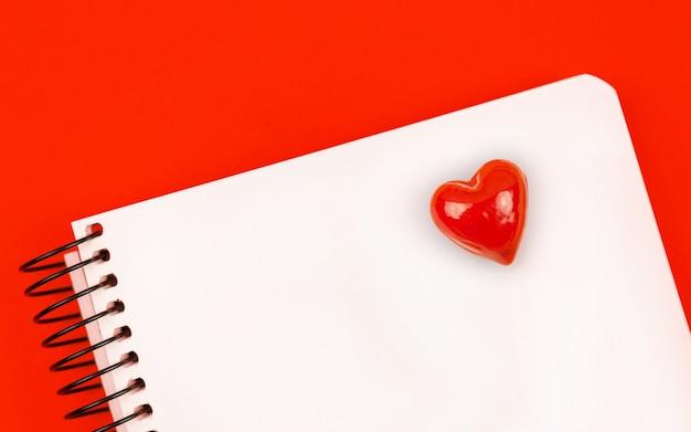 Caderno com coração vermelho, conceito de fundo de carta de amor com mesa vermelha e espaço de cópia, foto de vista superior
