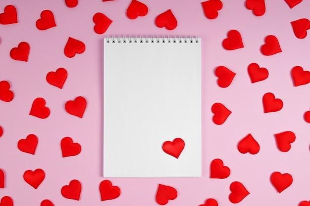 Caderno com corações vermelhos em um fundo rosa com corações. brincar.