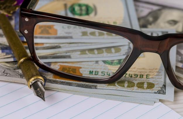 Caderno com dólares, caneta e óculos contabilidade de negócios financeiros