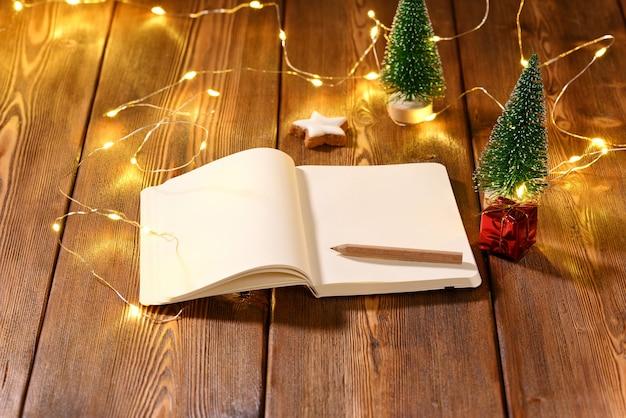 Caderno com espaço para texto sobre o tema de natal na mesa de madeira