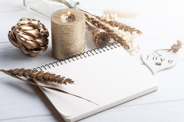 Caderno com flores douradas secas e vela acesa
