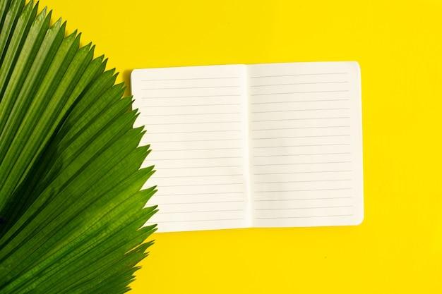 Caderno com folha de palmeira tropical em amarelo