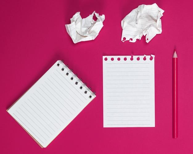 Caderno com folhas brancas e uma folha de papel amassada arrancada